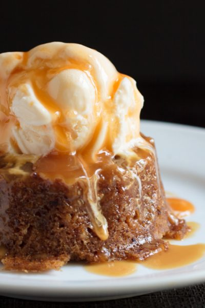 Sticky toffee pudding cake on a plate with vanilla ice cream and caramel sauce on top