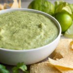 creamy salsa verde in a bowl surrounded by avocados, chips and tomatillos