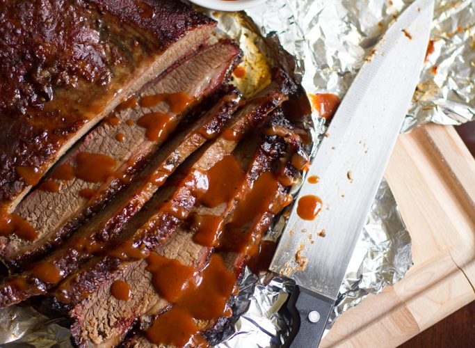 Savory brisket slow smoked on the grill, Texas style! All you need is salt, pepper and a big ol' hunk of meat.
