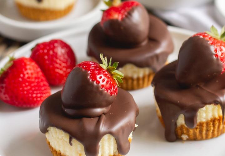 mini cheesecakes on a plate with chocolate covered strawberries on top and chocolate dripping down