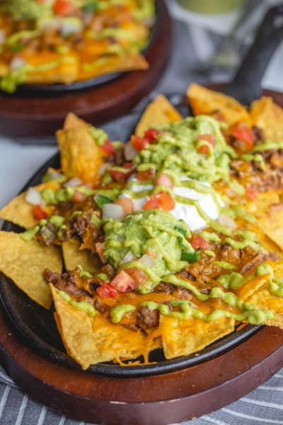 restaurant style beef nachos in a cast iron skillet topped with cheese, tomatoes, guacamole and more