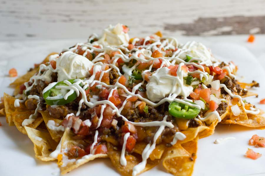 Dumpster Fire Nachos. The perfect party food for any gathering, piled high with all kinds of junk, including fiery jalapeno ranch.