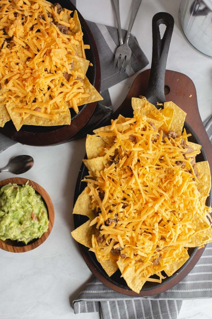 chips in a skillet topped with beans, beef and shredded cheese