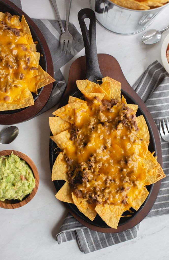 chips in a skillet topped with beans, beef and melted cheese