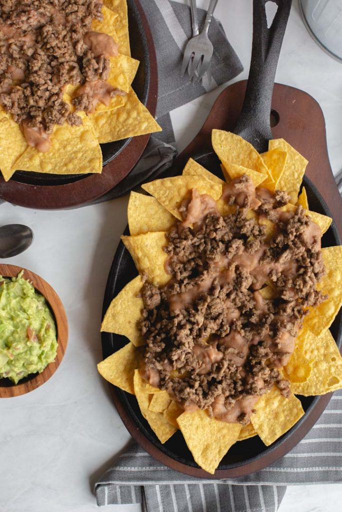 chips in a skillet topped with beans and beef