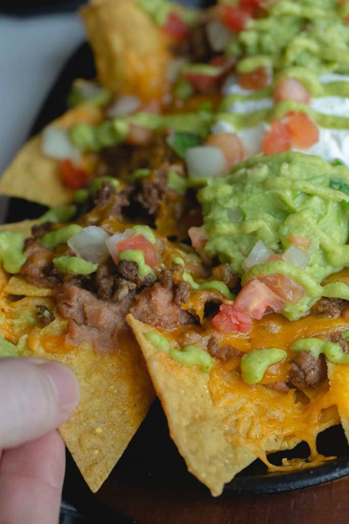 a finger pulling out a chip on nachos