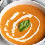 Roasted Red Pepper and Tomato Soup garnished with a basil leaf and swirl of cream