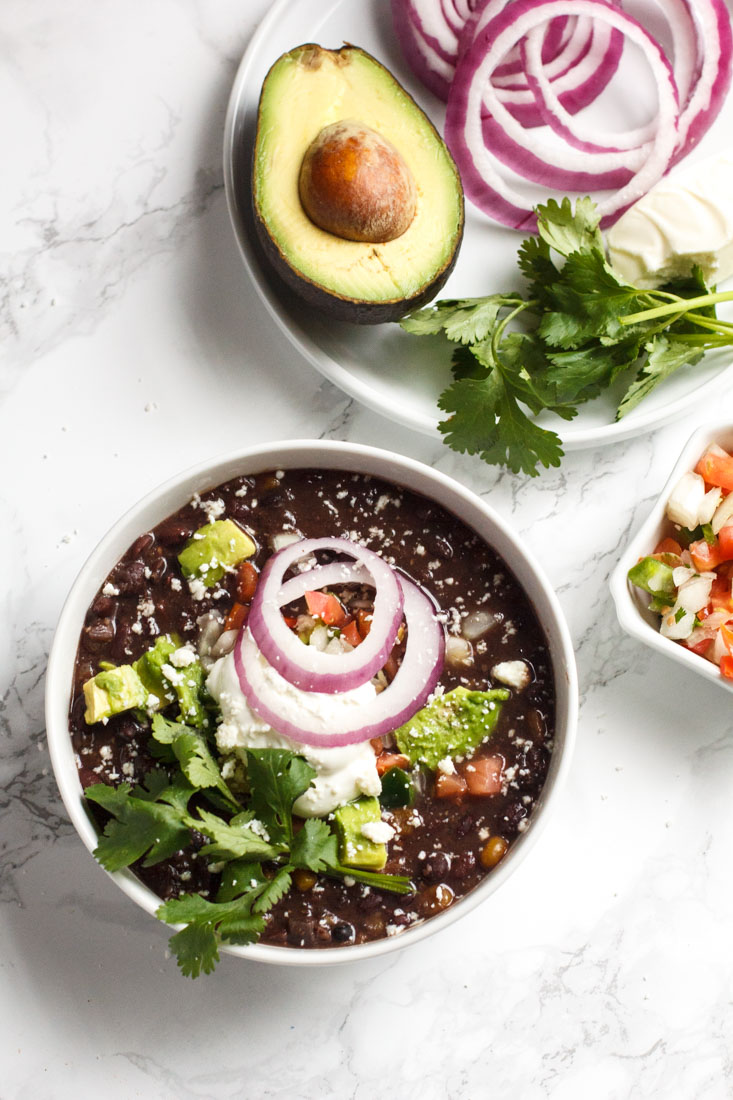 slow cooker black bean soup in a bowl with cilantro, avocado and sour cream