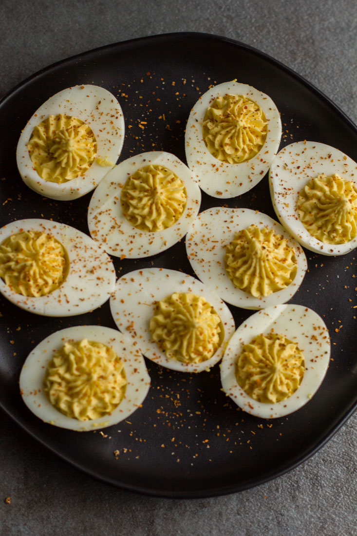 plain deviled eggs on a black plate