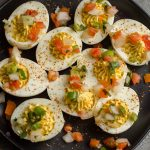 deviled eggs on a black plate topped with pico de gallo