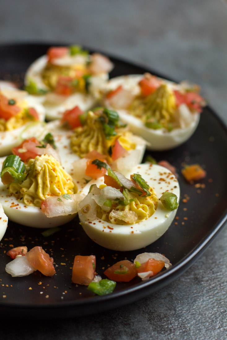hard boiled deviled eggs on a black plate with tomato and onion on top