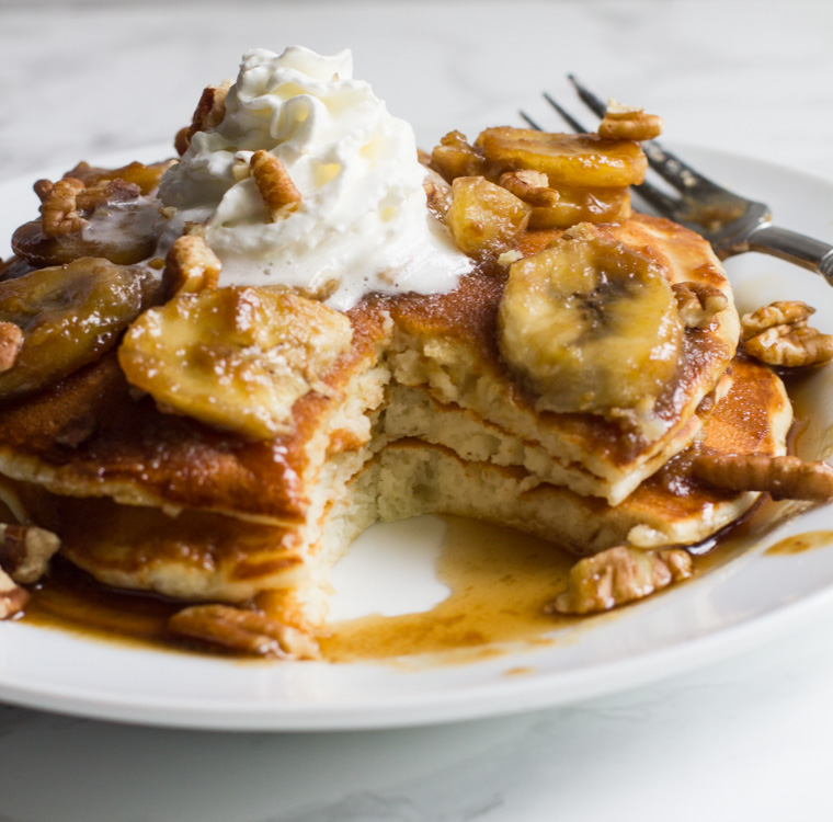The breakfast in bed of your dreams, these bananas foster pancakes are topped with a rich caramel sauce and served with pecans, whipped cream or vanilla ice cream.