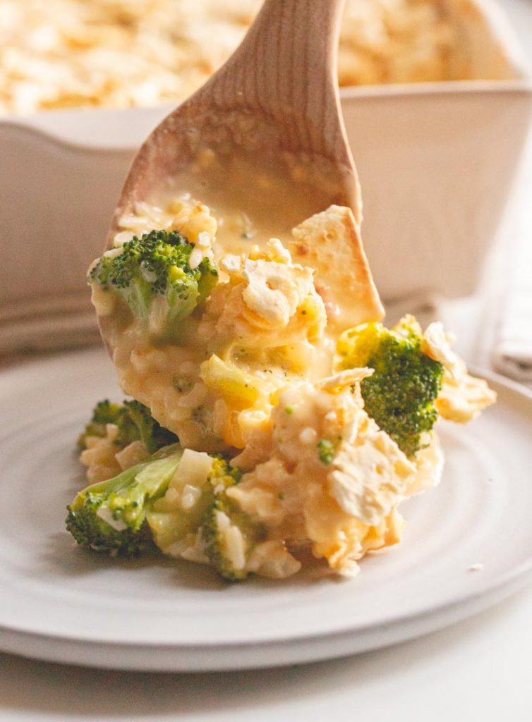 a spoonful of broccoli cheddar casserole being put on a plate