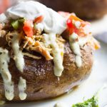 These easy baked potatoes are topped with a slow cooked Tex Mex style pulled pork, cheese, pico de gallo and jalapeno ranch. A hearty and easy to prepare meal!