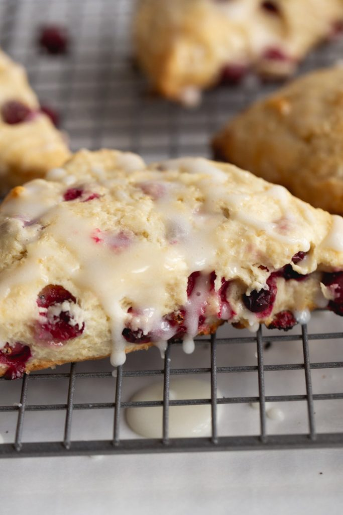 cranberry scone on a cooling rack with glaze