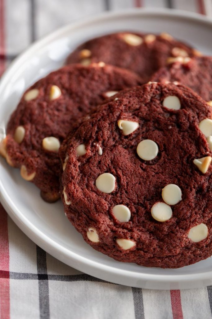 red velvet cookies with white chocolate chips on a plate on top of a towel