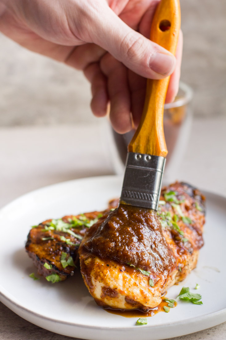 plate with chicken being brushed with bbq sauce