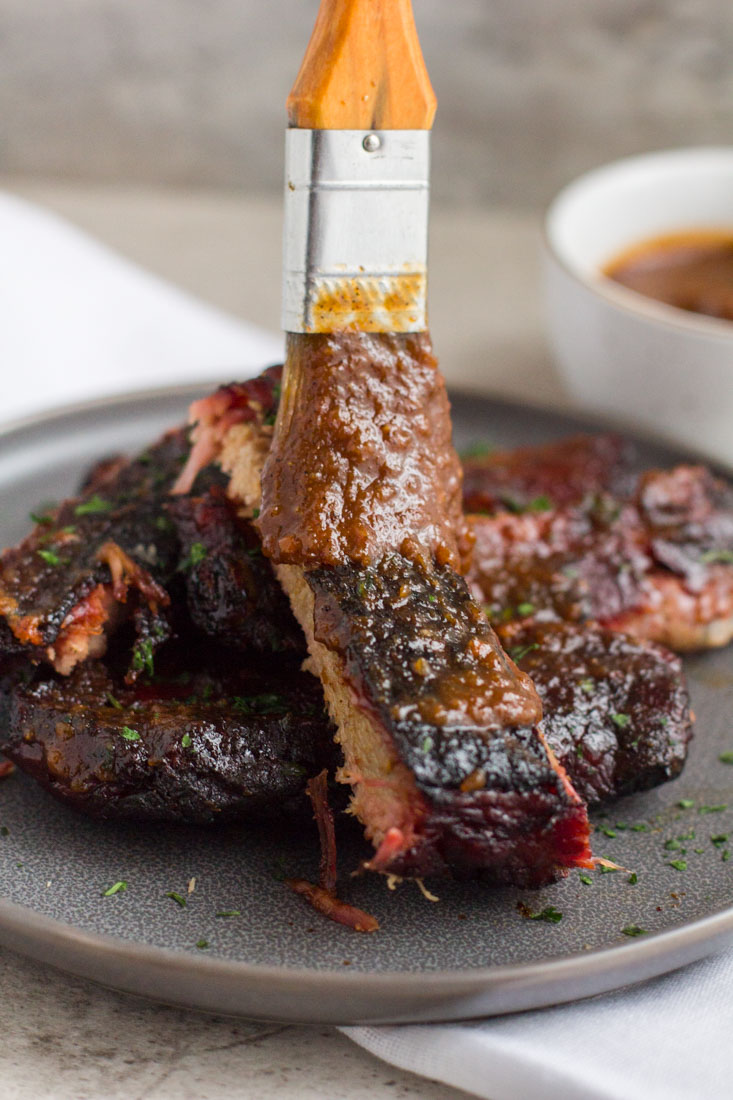 ribs being brushed with sauce