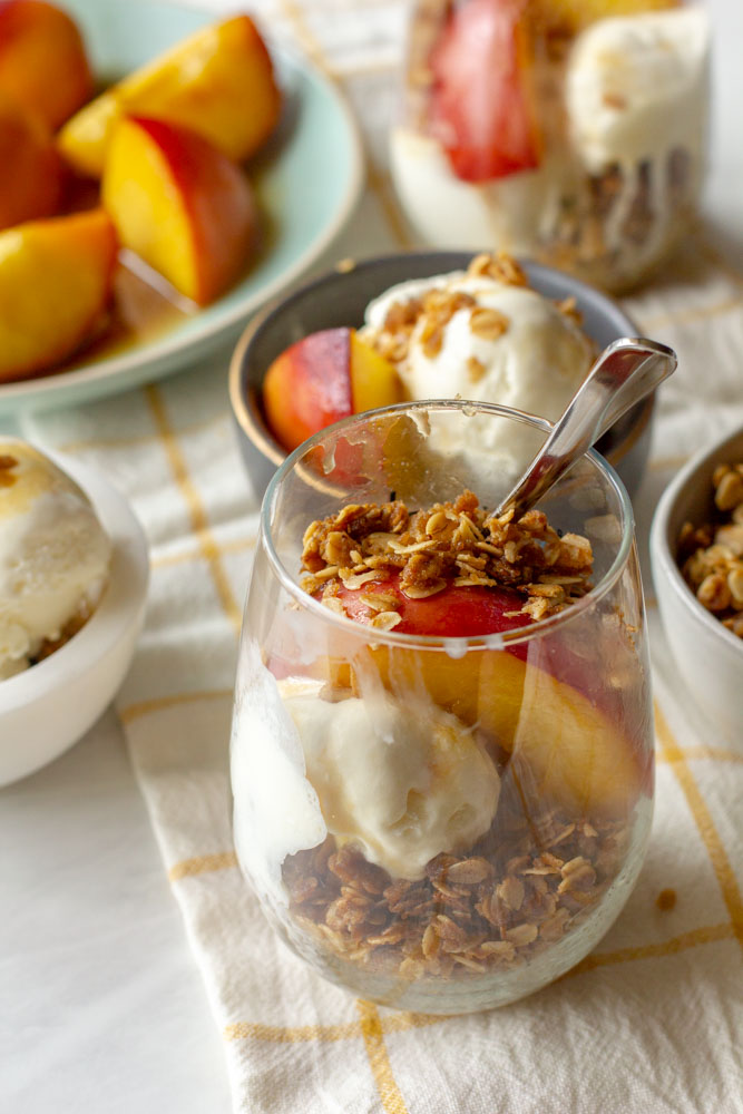 peach sundae on a table with honey, ice cream and toasted oats