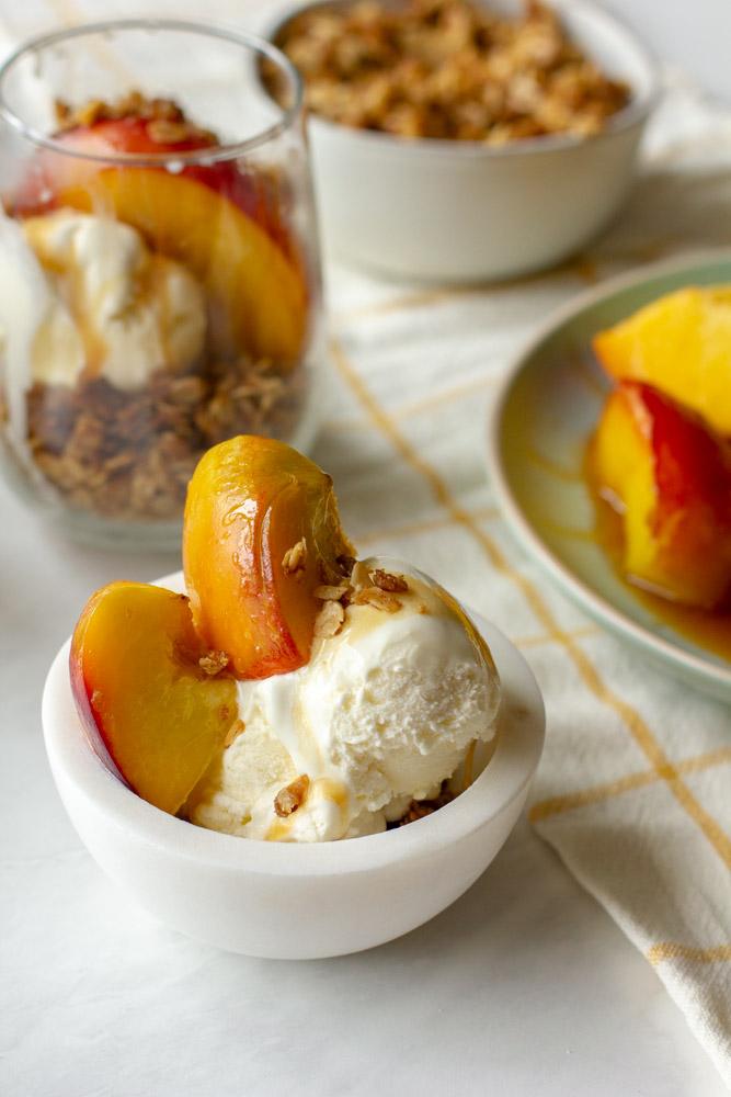 peach sundae on a table with ice cream, honey and oats