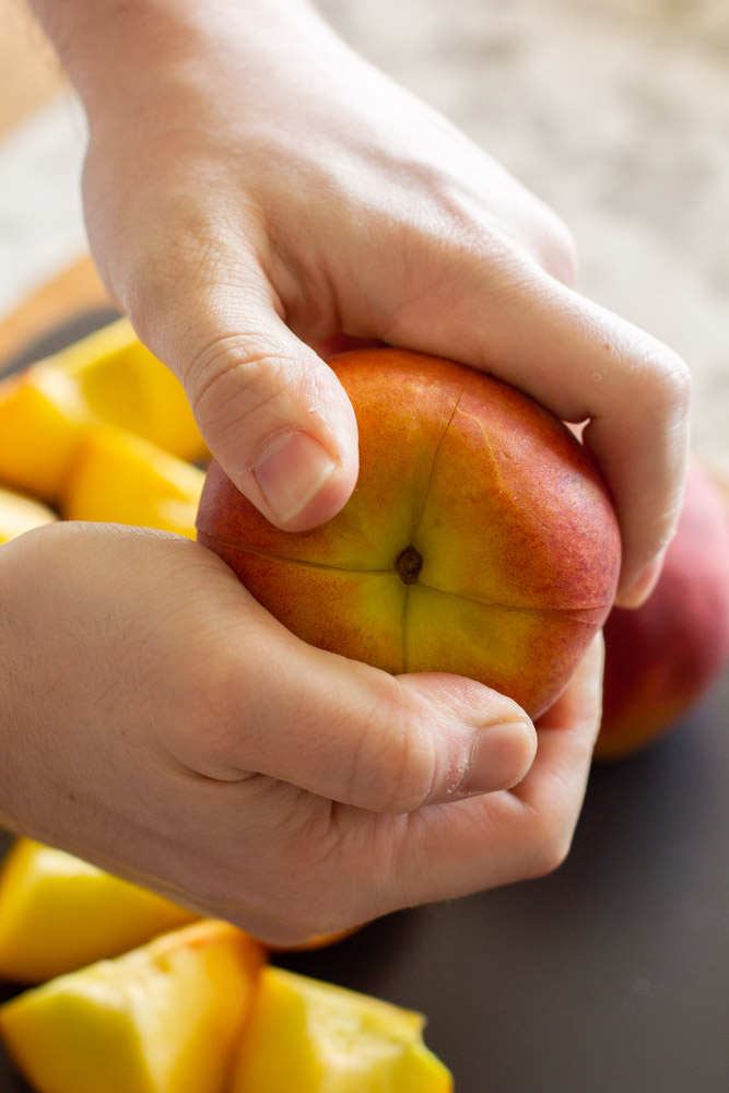 hands holding a peach and twisting apart