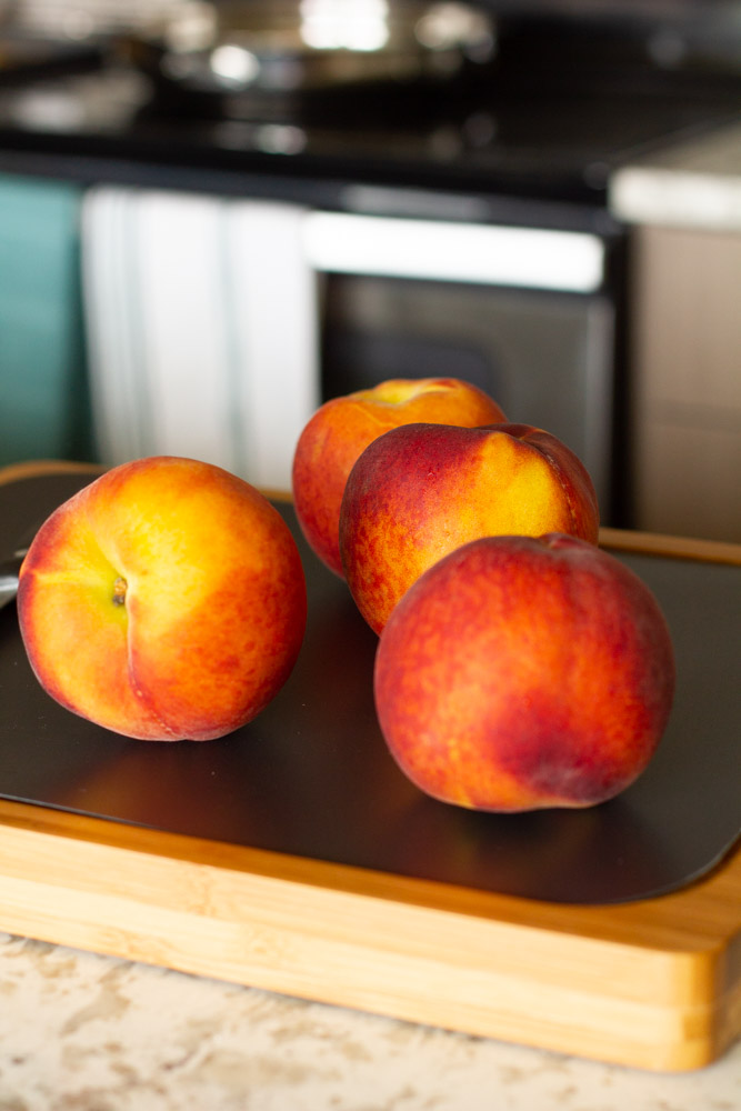 peaches on a cutting board in a kitchen