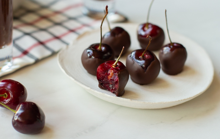 wine soaked chocolate covered cherries on a plate