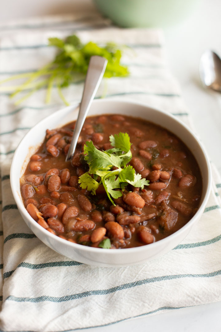 Instant Pot Charro Beans in a white bowl with cilantro on top