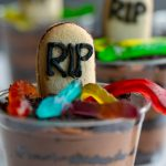 baileys chocolate mousse cups with layers of oreo dirt, gummy worms and a cookie tombstone