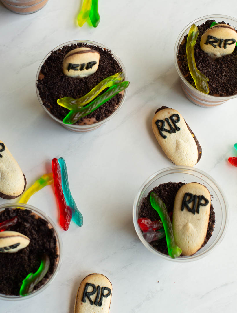 baileys chocolate mousse cups on a table with oreo dirt, gummy worms and tombstone cookies