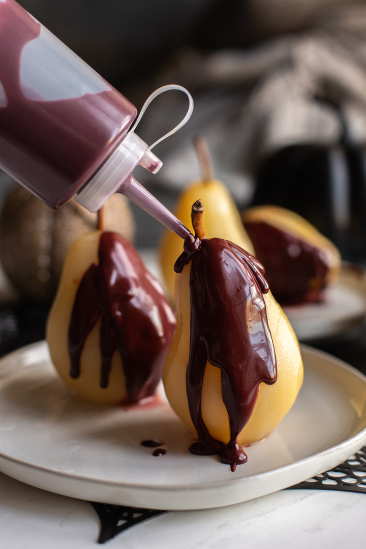 easy poached pears on a plate with red velvet sauce being applied with a squeeze bottle