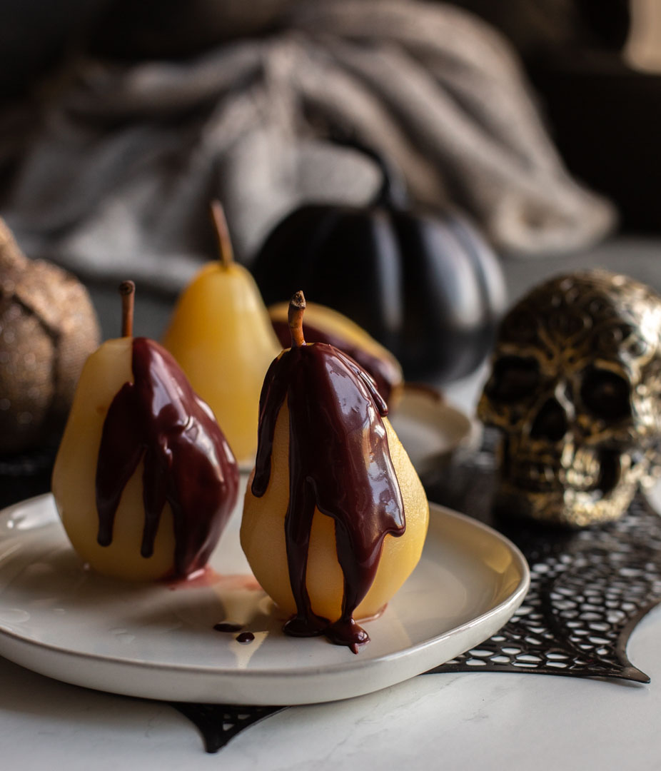 Easy Poached Pears on a dish with red velvet sauce