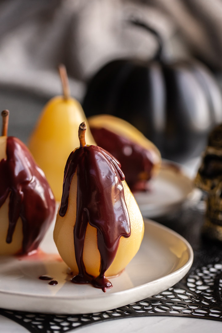 Easy Poached Pears on a plate with red velvet sauce