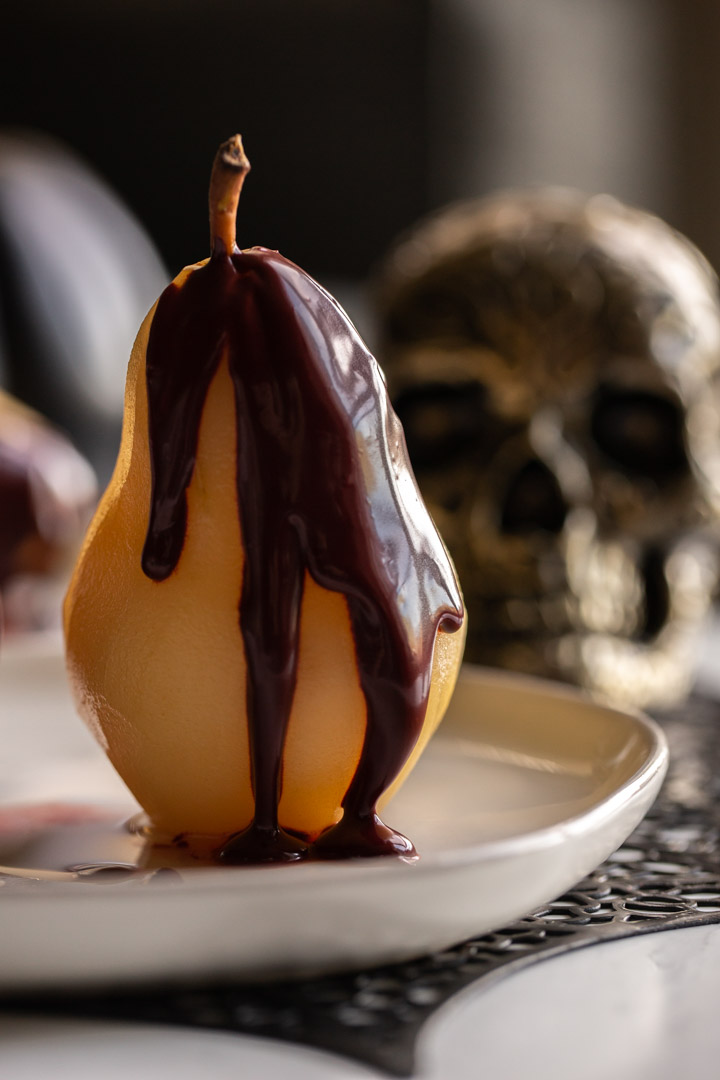 Easy poached pears sitting on a dish with red velvet sauce on top.
