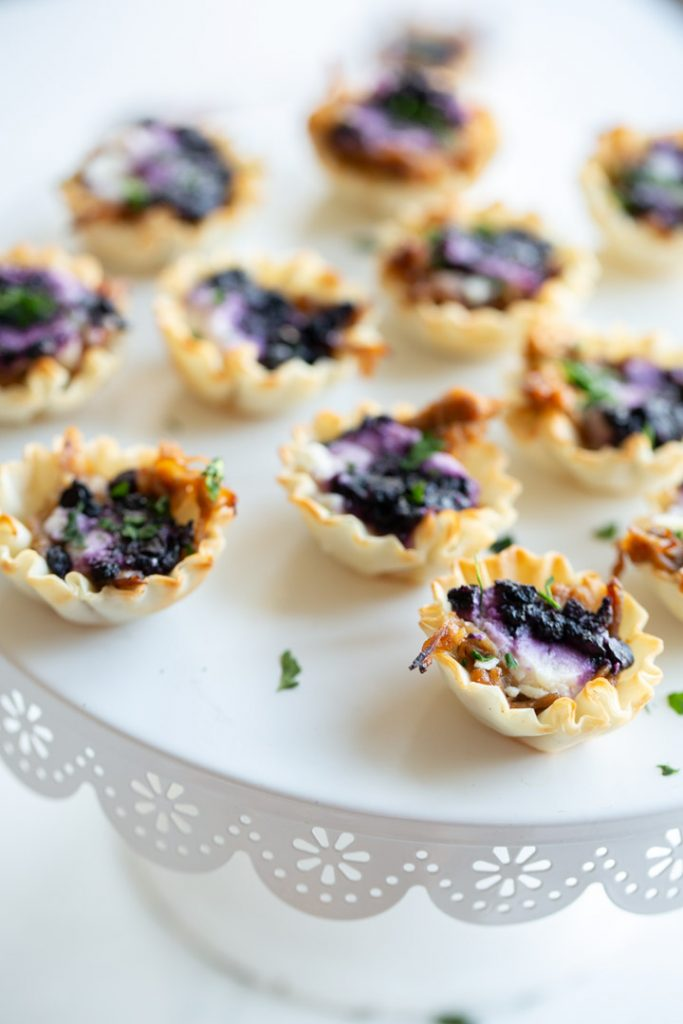 blueberry goat cheese appetizer bites in phyllo dough on a serving dish