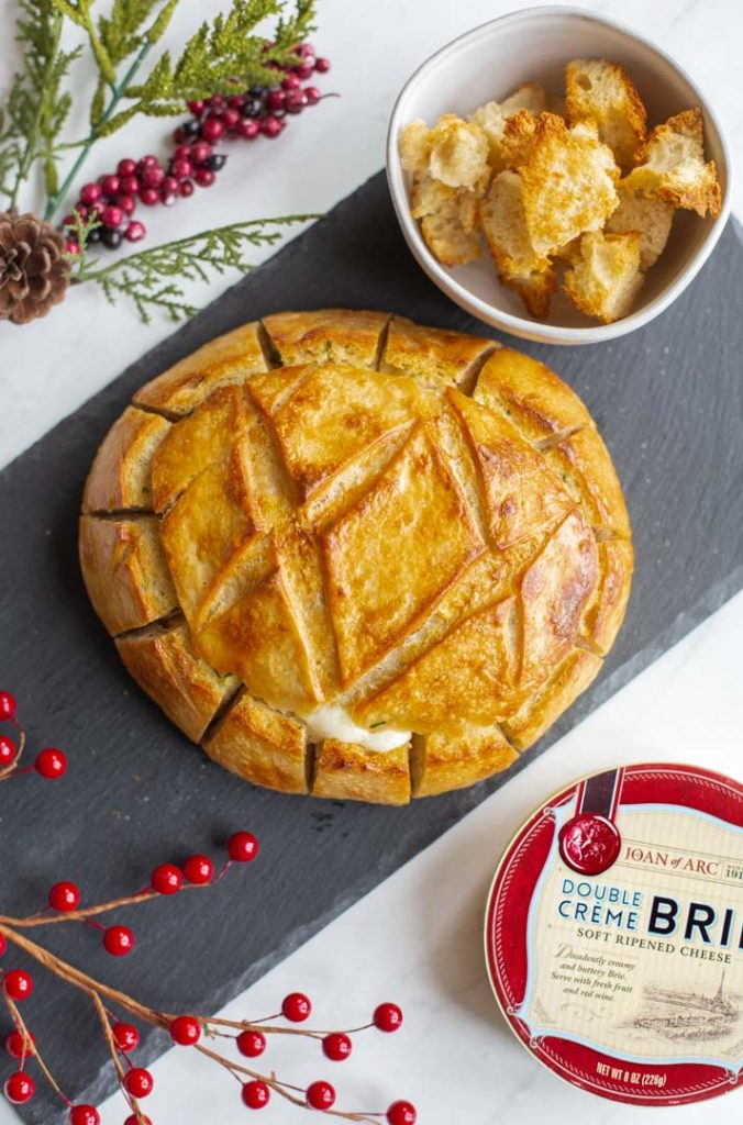 baked brie with cranberries with the edges cut into a pull apart bread