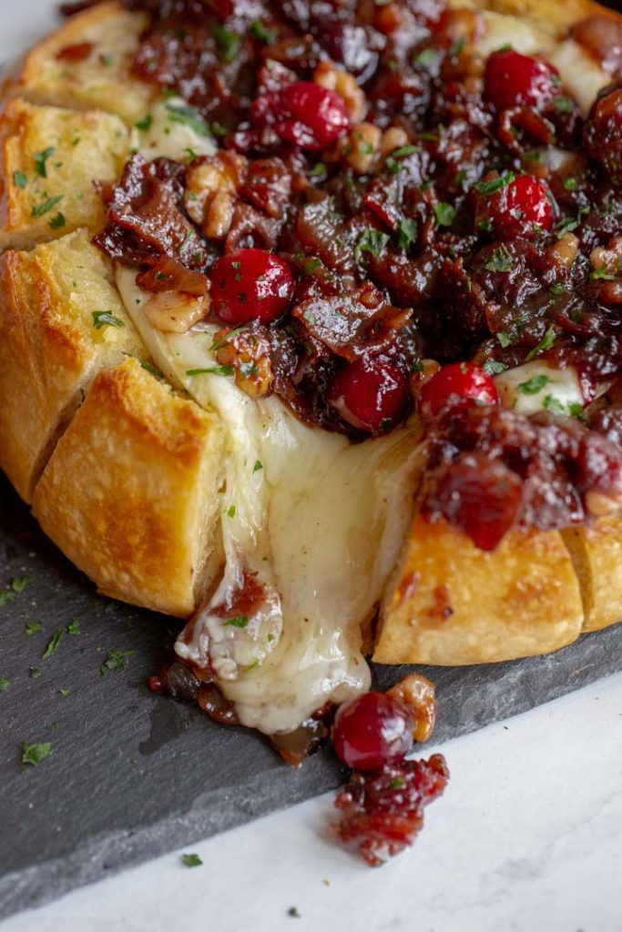 baked brie with cranberries and bacon on a plate with brie oozing out