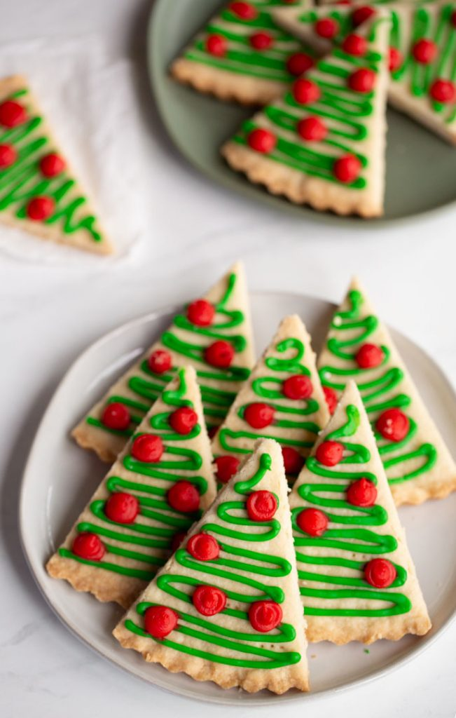 shortbread cookies cut into triangles and iced to look like christmas tree cookies