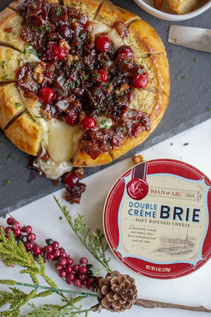 baked brie with cranberries and bacon with joan of arc brie on the table