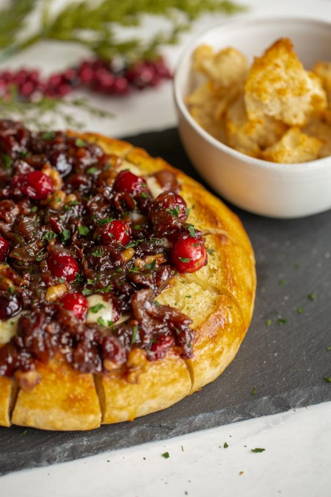 baked brie with cranberries and bacon on a plate with bread crumbs for serving