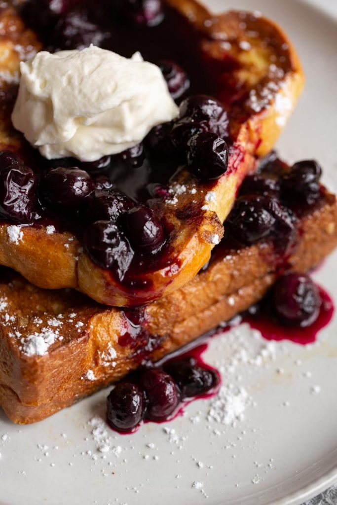 a closeup of blueberry stuffed french toast with blueberry sauce and cream on top