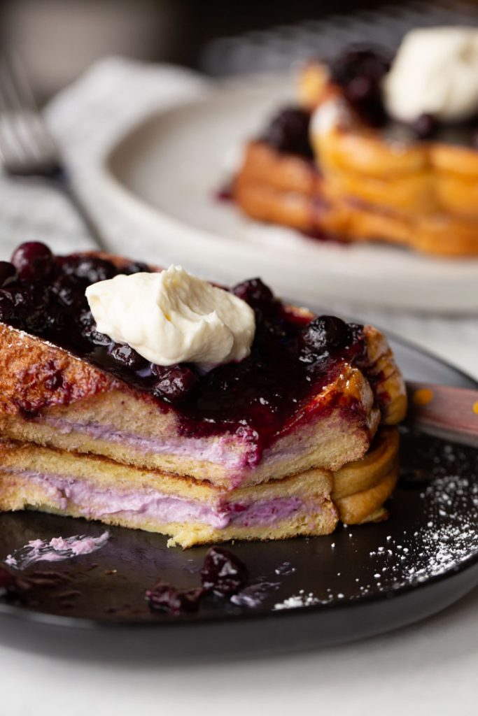 stuffed french toast with the blueberry cream cheese filling showing