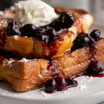 A delicious brioche french toast stuffed with blueberry cream cheese and topped with blueberry syrup. It's a gorgeous dish that makes breakfast extra special!