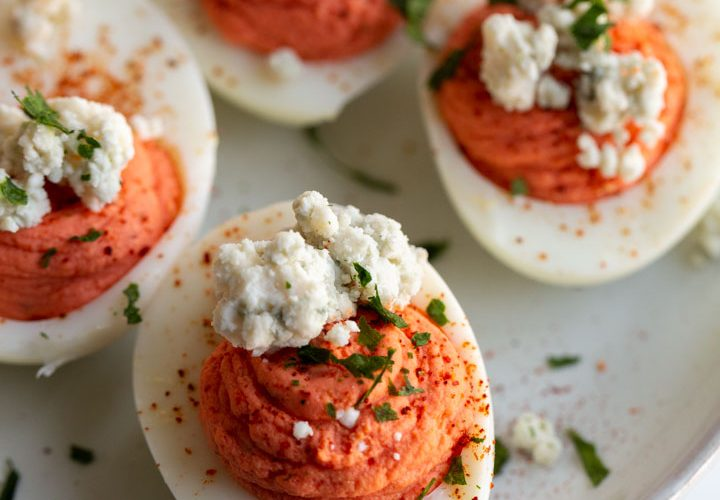 buffalo deviled eggs on a plate topped with blue cheese