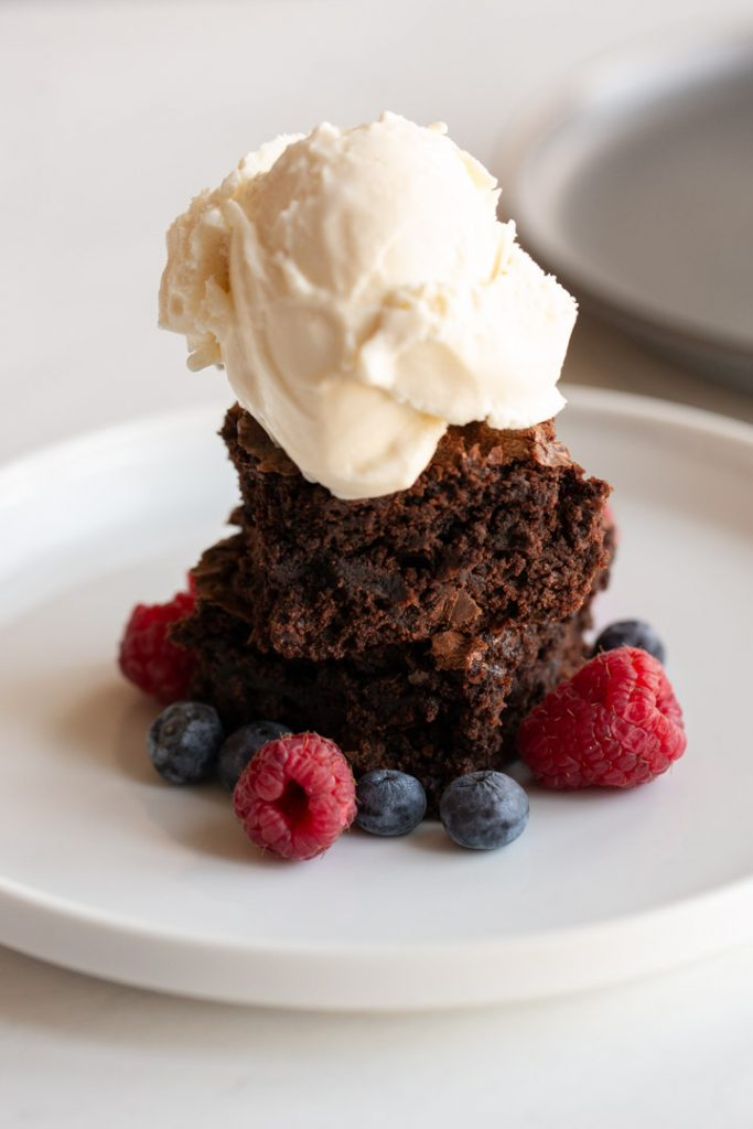 brownies ice cream and fruit on a plate