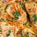 pan seared salmon served in a creamy sauce with spinach and tomatoes