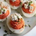 This recipe for buffalo deviled eggs has a spicy, tangy buffalo filling and blue cheese topping. It's great for serving at Easter, Independence Day, on game night or just to share with family and friends!