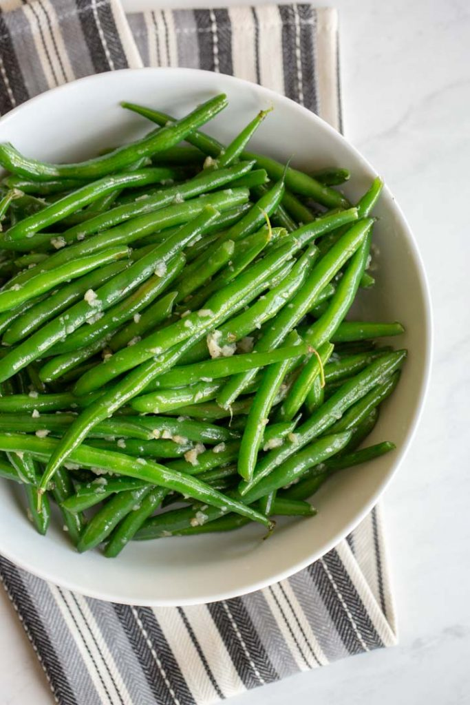 garlic green beans in a bowl on a towel