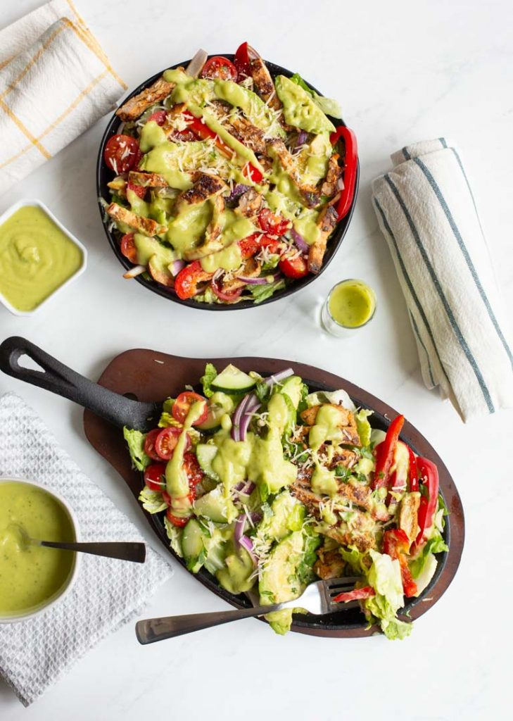 fajita chicken salad with tomatoes, onions and peppers topped with avocado lime dressing