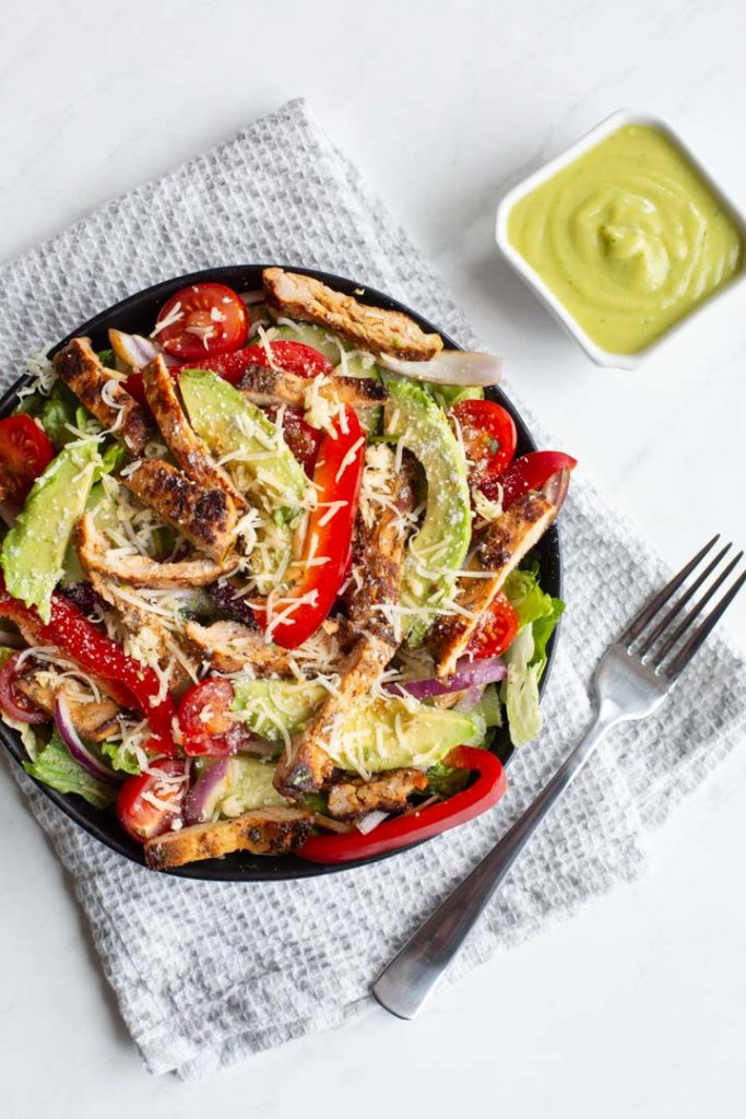 grilled chicken fajita salad with peppers, onions, avocado, tomatoes and cheese